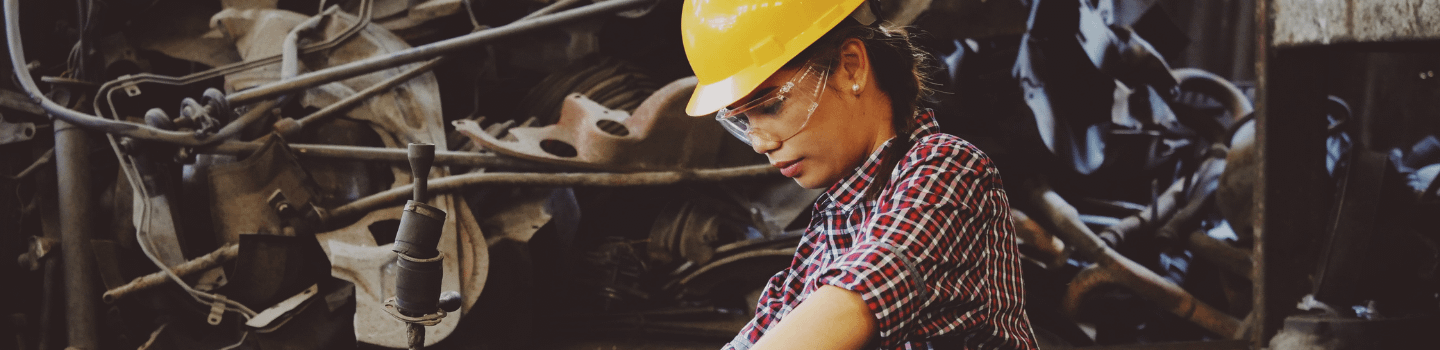 A woman wearing a checkered shirt, yellow hard hat, and protective eyeglasses leans over machinery